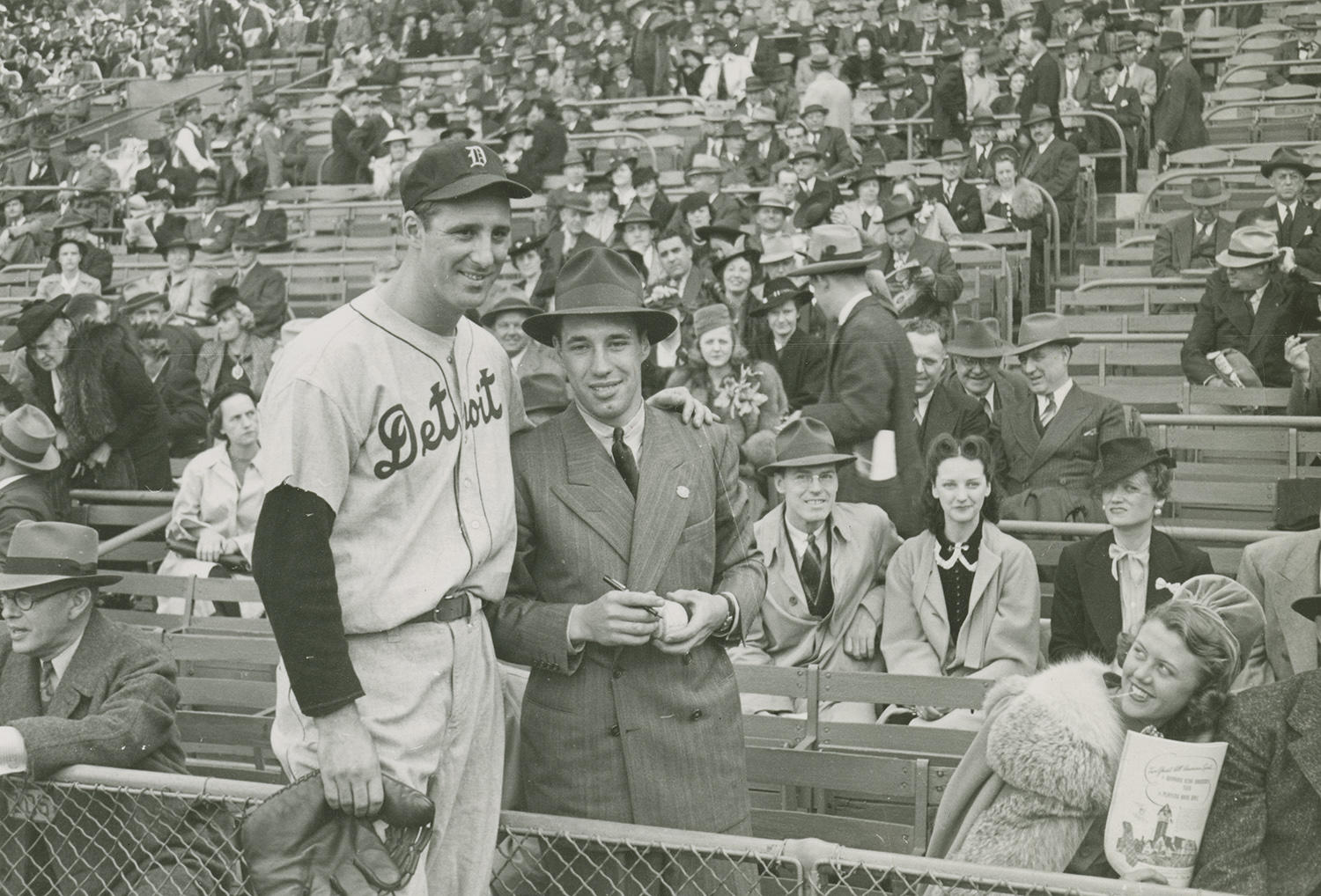 """Bob Feller poses for a photograph with Detroit Tigers' star Hank Greenberg. Feller, standing on the spectator side of the fence, is seen holding a baseball and marker, waiting for an autograph. <a href=""""https://collection.baseballhall.org/islandora/object/islandora%3A612130"""">PASTIME</a> (National Baseball Hall of Fame and Museum)"""