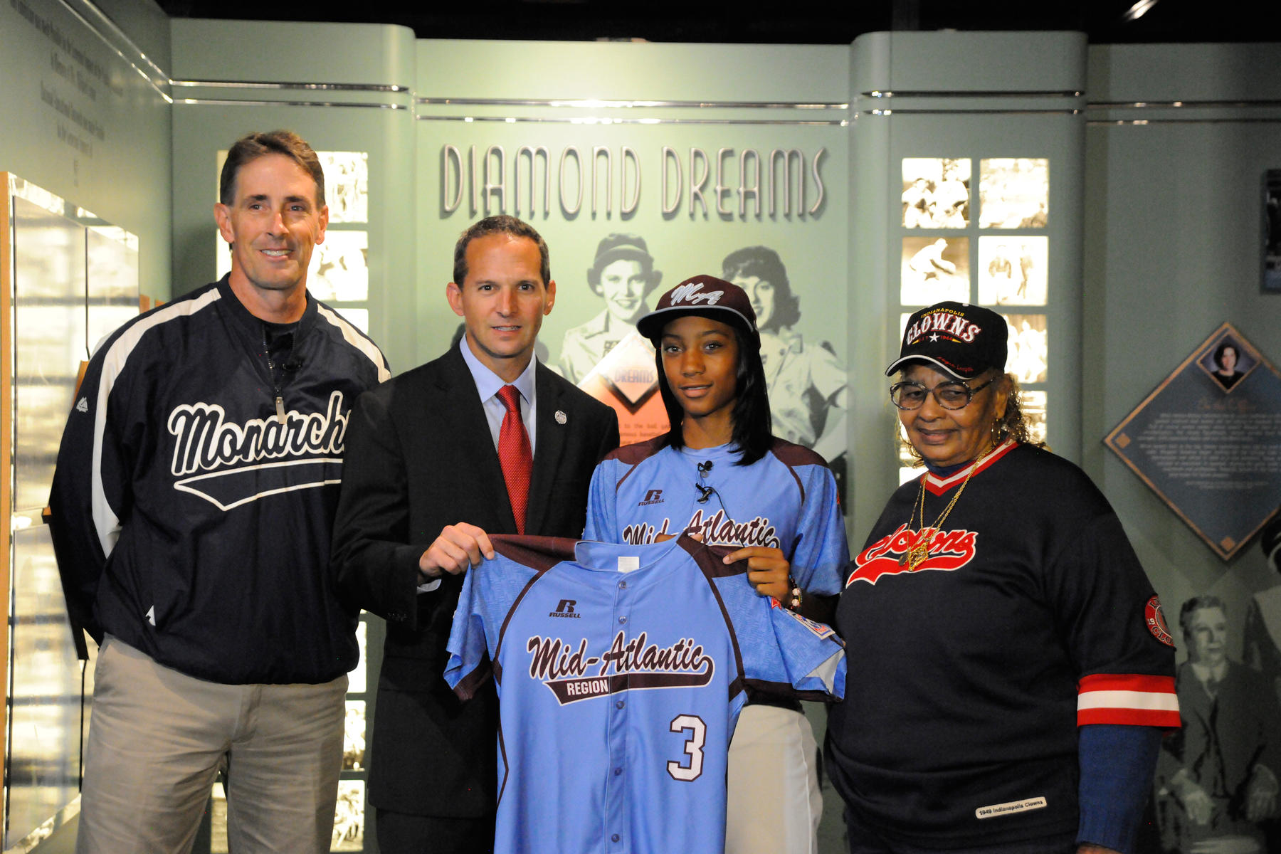 """Mo'ne Davis donated a jersey she wore at the 2014 Little League Baseball World Series. She is seen here with (left to right) Steve Bandura, founder/coach of the Anderson Monarchs, Hall of Fame President Jeff Idelson and Mamie """"Peanut"""" Johnson, one of just three women in play in the Negro Leagues. (Milo Stewart, Jr. / National Baseball Hall of Fame)"""