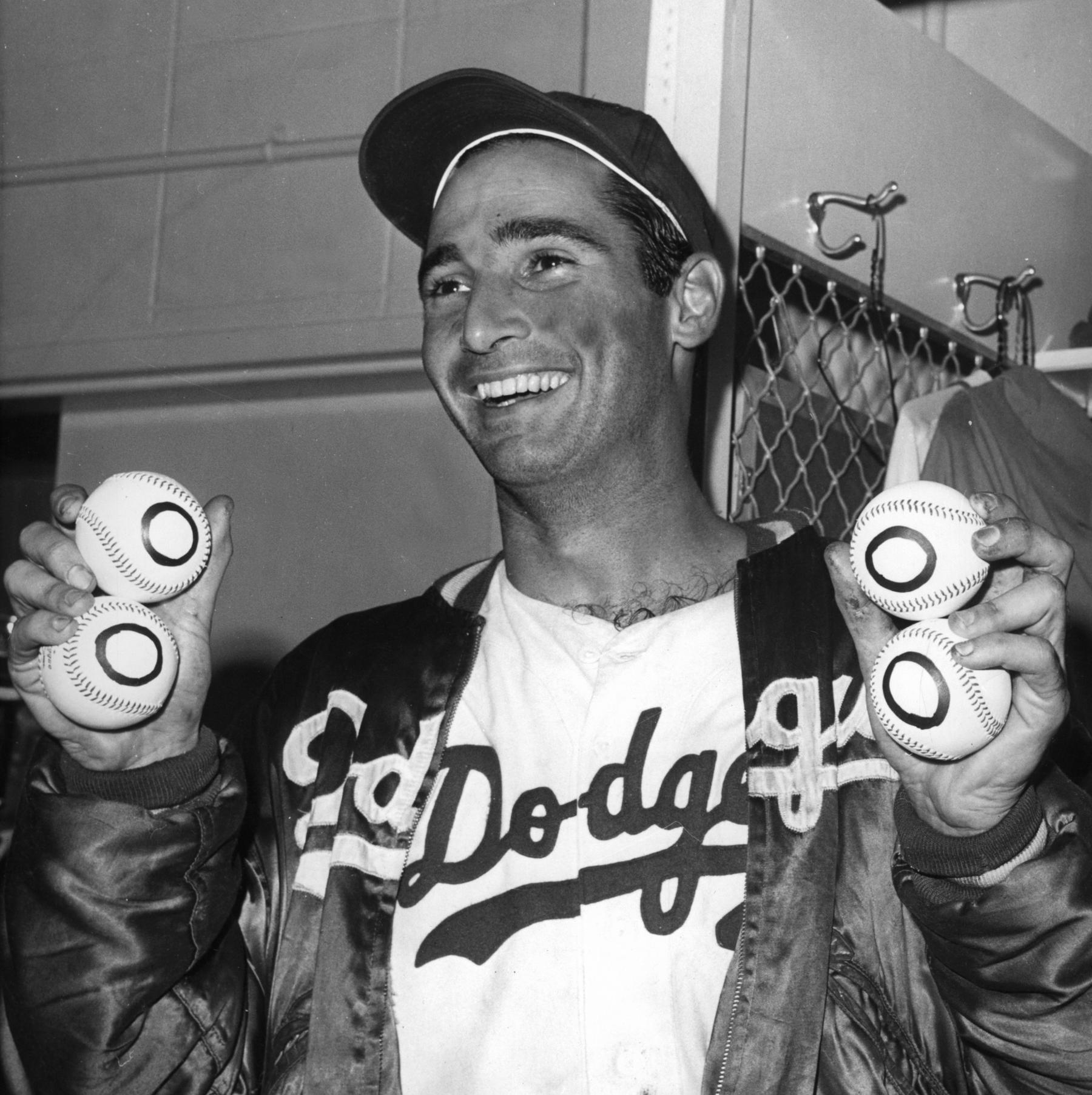 Sandy Koufax holding four balls to signify his fourth career no-hitter. He achieved this feat on September 9th, 1965. BL-305.65 (National Baseball Hall of Fame Library)