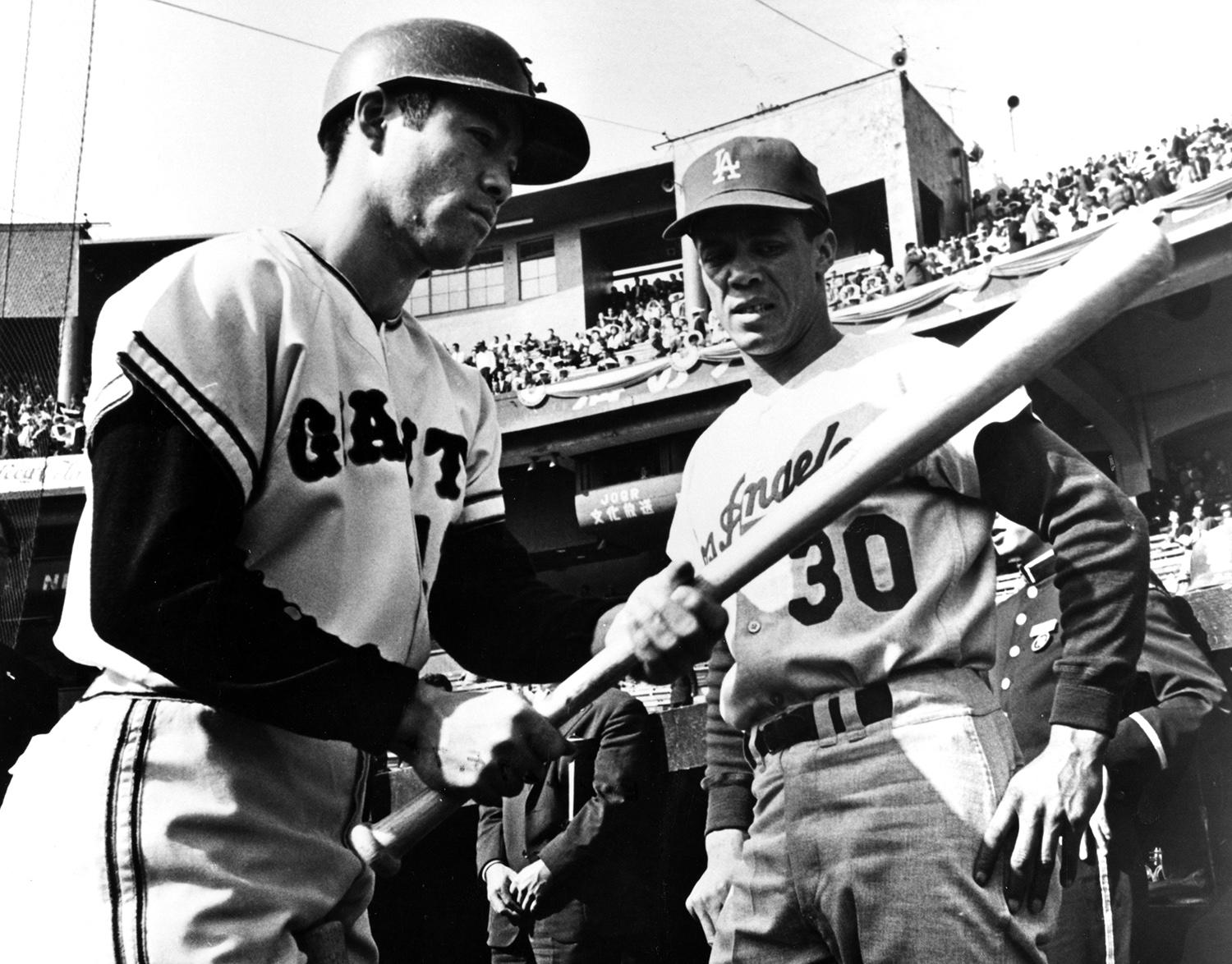 """Pictured above, Maury Wills of the Los Angeles Dodgers (right) talks to a Japanese baseball player during the Dodgers tour of Japan following the 1966 season. Wills embarked on the 1966 tour, but had to leave early for a treatment on his injured leg. <a href=""""http://collection.baseballhall.org/islandora/object/islandora%3A273641"""">PASTIME</a> (National Baseball Hall of Fame)"""