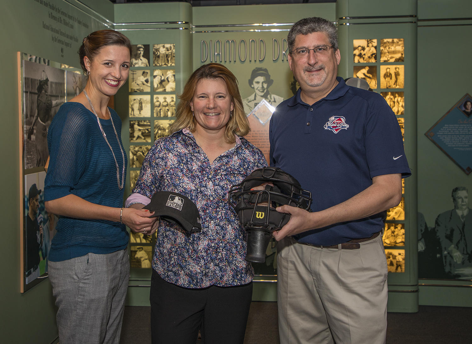 Jen Pawol poses with her artifacts in the <em>Diamond Dreams</em> exhibit at the Hall of Fame, alongside assistant curator Gabrielle Augustine (left) and vice president, exhibitions & collections Erik Strohl (right). (By Photographer Milo Stewart Jr./National Baseball Hall of Fame and Museum)