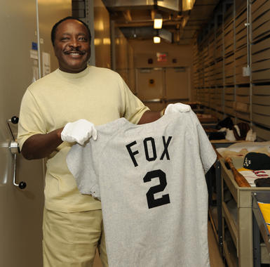 Joe Morgan holds a jersey of one of his heroes, Hall of Fame second baseman Nellie Fox, during a tour of the Museum archives. (Milo Stewart Jr./National Baseball Hall of Fame and Museum)