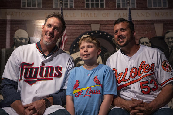 Joe Nathan (left) and John Parrish pose with a young fan at the Hall of Fame's <em>Night at the Museum</em> event following the 2019 Hall of Fame Classic. (Milo Stewart Jr./National Baseball Hall of Fame and Museum)