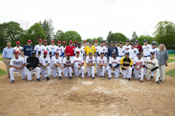 Members of Team Rollie and Team Goose pose for a photo on Doubleday Field with Hall of Fame Chairman of the Board Jane Forbes Clark (far right) and former Hall of Fame President Jeff Idelson (far left) following the 2019 Hall of Fame Classic. (Milo Stewart Jr./National Baseball Hall of Fame and Museum)
