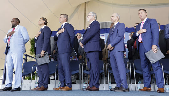 Vladimir Guerrero, Trevor Hoffman, Chipper Jones, Jack Morris, Alan Trammell and Jim Thome stand during the national anthem at the 2018 Hall of Fame <em>Induction Ceremony</em>.