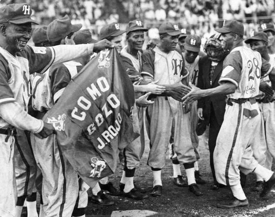 Art Pennington, number 28 at the far right, is greeted by teammates after hitting a grand slam home run in Cuba.  BA-SCR-2-005  (National Baseball Hall of Fame)
