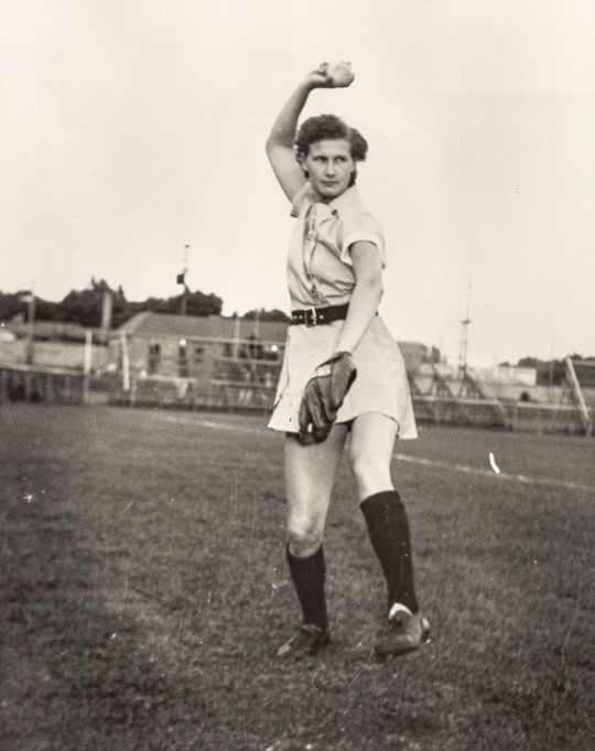 A photograph depicting Connie Wisniewski pitching underhand. Her right arm is raised over her head at the top of her windmill pitching motion. (National Baseball Hall of Fame and Museum)