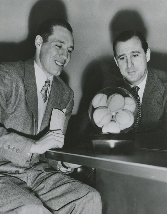 """Bob Feller with Hank Greenberg, general manager of the Cleveland Indians. Both men pose for a photograph after Feller signed his 13th contract with the Indians for $50,000, making him the highest paid pitcher in the American League. <a href=""""https://collection.baseballhall.org/islandora/object/islandora%3A610689"""">PASTIME</a> (National Baseball Hall of Fame and Museum)"""