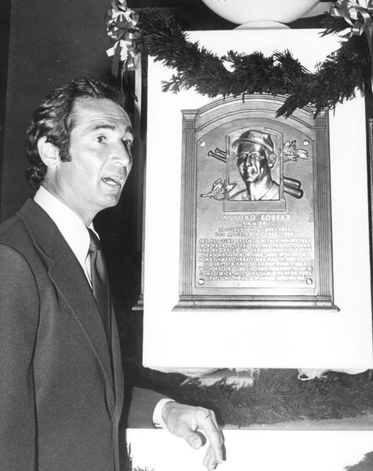 Hall of Fame Class of 1972 member Sandy Koufax poses next to his plaque. (National Baseball Hall of Fame and Museum)