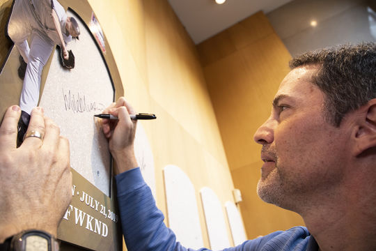 Mike Mussina signs his plaque backer as part of his Orientation Visit in March of 2019. (Milo Stewart Jr./National Baseball Hall of Fame and Museum)