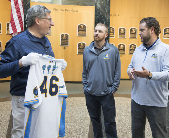 Erik Strohl, the Museum's vice president of exhibitions and collections, accepts a Myrtle Beach Pelicans jersey featuring American Sign Language characters from Ryan Cannella, the corporate marketing managers of the Pelicans (center), and Ryan Moore, the Pelicans' general manager, on Oct. 5 in Cooperstown . (Milo Stewart Jr./National Baseball Hall of Fame and Museum)