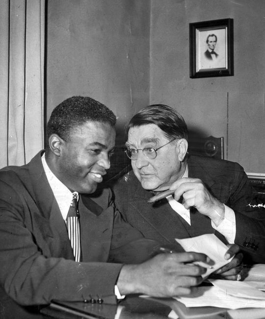 Jackie Robinson (left) signed a contract with Branch Rickey's Dodgers organization in 1945. (National Baseball Hall of Fame and Museum)