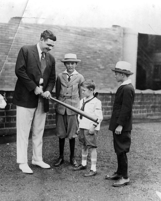 Babe Ruth showing children how he holds a bat in a 1921 photograph.  Ruth always had time for children, who were drawn to him as much as he was to them. (National Baseball Hall of Fame Library)