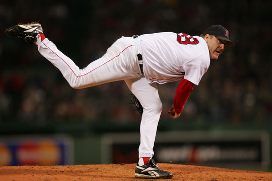 "Curt Schilling delivers a pitch in Game Two of the 2004 World Series with both the bloody sock and ""K ALS"" mark visible near his right ankle. HY6N2184 (Brad Mangin / MLB)"