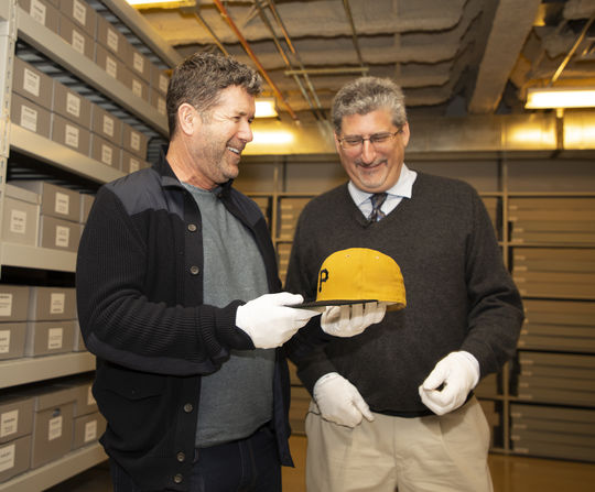 Hall of Fame vice president of exhibitions and collections Erik Strohl, right, shows Edgar Martinez the cap that Roberto Clemente wore when the Pirates' star recorded his 3,000th career hit in 1972. Clemente was Martinez's hero growing up in Puerto Rico. (Milo Stewart Jr./National Baseball Hall of Fame and Museum)